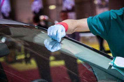 A man replacing a car windshield.
